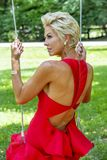 Schitterend Blonde Modelposing outdoors wearing een Rode Avondtoga stock afbeelding