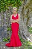 Schitterend Blonde Modelposing outdoors wearing een Rode Avondtoga royalty-vrije stock afbeelding