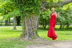 Schitterend Blonde Modelposing outdoors wearing een Rode Avondtoga stock foto