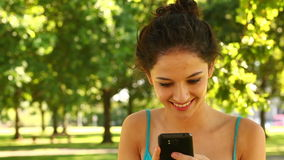 Schitterend brunette die een tekst in het park verzenden stock video
