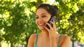 Schitterend brunette die in het park telefoneren stock footage