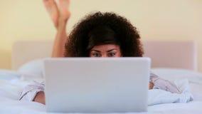 Schitterend brunette die op bed liggen die laptop met behulp van stock videobeelden