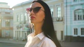 Schitterend brunette die zonnebril in zonstralen dragen stock video