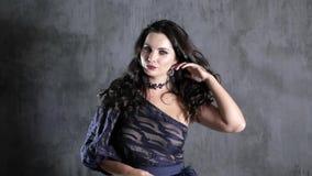 Schitterend brunette met mooi haar en halsband op hals op achtergrond van grijze muur stock videobeelden