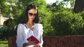 Schitterend die brunette van lezingsboek wordt gebeëindigd in het park stock video