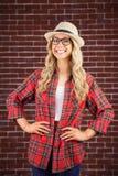 Schitterend glimlachend blonde hipster met handen op heupen stock afbeelding