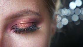 Schitterend groen oog van Kaukasische vrouwen dichte omhooggaande, rode make-up en zwarte achtergrond, manier vibes stock footage