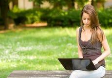 Schitterend jong donkerbruin meisje dat haar laptop met behulp van Stock Foto