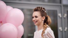 Schitterend jong meisje met bloemen in haar met roze luchtballons stock videobeelden