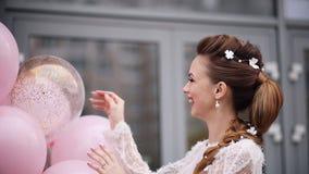 Schitterend jong meisje met bloemen in haar met roze luchtballons stock video