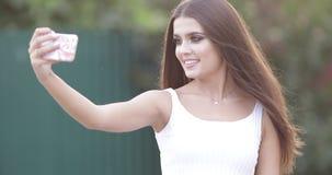 Schitterend Kaukasisch meisje met kapsel die in sensuele kleding selfie in de tuin maken stock video
