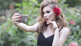 Schitterend Kaukasisch meisje met kapsel die in sensuele kleding selfie in de tuin maken stock footage