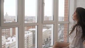 Schitterend Kaukasisch mooi meisje met het perfecte lichaam laing tegen het venster in de zon stock videobeelden