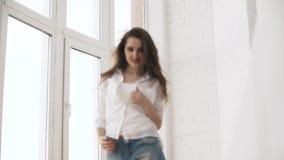 Schitterend Kaukasisch mooi meisje met het perfecte lichaam laing tegen het venster in de zon stock footage