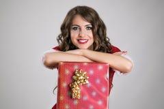 Schitterend Kerstmanmeisje die op de grote rode giftdoos rusten met gouden lint die camera bekijken Stock Afbeeldingen