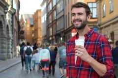 Schitterend mannetje die een beschikbare kop van koffie in overvolle stadsstraat houden royalty-vrije stock foto's