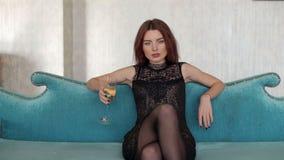 Schitterend meisje met champagnezitting op de mooie bank stock videobeelden