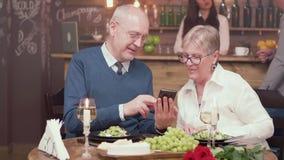 Schitterend oud paar op een datum in uitstekend restaurant die door foto's op een smartphone kijken stock footage