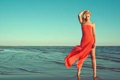 Schitterend sexy slank blond model in rode strapless kleding met vliegende trein die zich op tiptoe in het zeewater bevinden royalty-vrije stock afbeelding