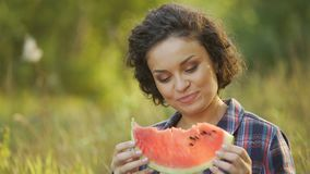 Schitterend wijfje die verse en sappige watermeloen in de achtertuin eten, gezond voedsel stock videobeelden
