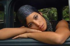 Schitterend zigeunermeisje die op de autodeur liggen