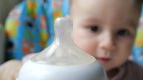 Schitterende babyzitting en uit het uitrekken van zijn handen aan een fles met melk stock video