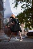 Schitterende ballerina in zwarte uitrusting die in de stadsstraten dansen stock fotografie