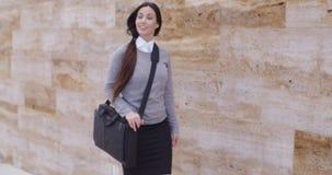 Schitterende bedrijfsvrouw die voorbij muur lopen stock video