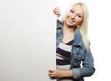 Schitterende blonde vrouw die op een raad richten terwijl status tegen Royalty-vrije Stock Foto's