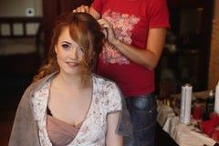 Schitterende bruid die haar die haar krijgen door professionele stilist Duitsland wordt gedaan stock fotografie