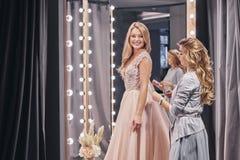 Schitterende Bruid Geconcentreerde jonge vrouw die bruid meten terwijl royalty-vrije stock afbeelding