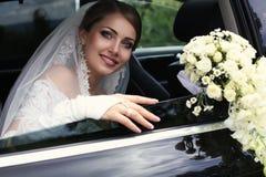 Schitterende bruid in huwelijkskleding met boeket van bloemen die in auto stellen Stock Afbeelding