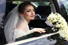 Schitterende bruid in huwelijkskleding met boeket van bloemen die in auto stellen Stock Fotografie