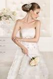 Schitterende bruid met witte kleding met bloemenboeket Stock Foto's
