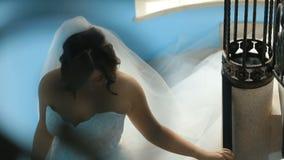 Schitterende charmante bruid in een luxueuze kleding die de treden dalen Mooi sensueel jong meisje in een witte toga met stock footage