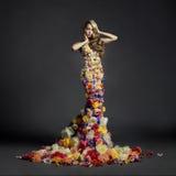 Schitterende dame in kleding van bloemen Stock Foto's