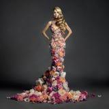 Schitterende dame in kleding van bloemen Stock Fotografie