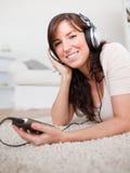 Schitterende donkerbruine vrouw die aan muziek luistert Royalty-vrije Stock Afbeelding