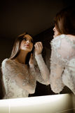 Schitterende donkerbruine vrouw met lang haar en blauwe ogen die zelf in de spiegel en make-up doen eruit zien Stock Fotografie