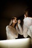 Schitterende donkerbruine vrouw met lang haar en blauwe ogen die zelf in de spiegel en make-up doen eruit zien Royalty-vrije Stock Foto's