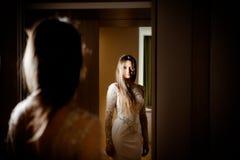 Schitterende donkerbruine vrouw met lang haar en blauwe ogen zelf die in de spiegel kijken Stock Afbeeldingen