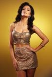 Schitterende donkerbruine vrouw met lang haar in rok en bustiere met gouden lovertjes Stock Foto