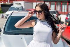 Schitterende donkerbruine vrouw in zonnebril en auto erachter stock foto