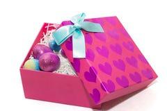 Schitterende eieren in heldere roze doos met harten op hoogste en blauwe B Stock Foto