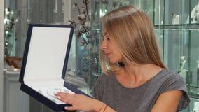 Schitterende gelukkige vrouw die aan de camera glimlachen die dure juwelenreeks houden stock footage