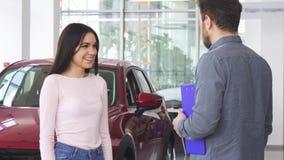 Schitterende gelukkige vrouw het schudden handen met autohandelaar na het ontvangen van autosleutels stock video