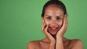 Schitterende gelukkige vrouw wat betreft haar gezicht die zacht aan de camera glimlachen stock video
