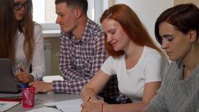 Schitterende gelukkige vrouwelijke student die aan de camera glimlachen, terwijl het bestuderen met vrienden stock videobeelden