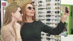 Schitterende gelukkige vrouwen die selfies terwijl eyewear winkelen nemen stock videobeelden