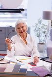 Schitterende glimlachende grijs-haired ontwerper met toebehoren die aan projecttekening werken royalty-vrije stock foto's